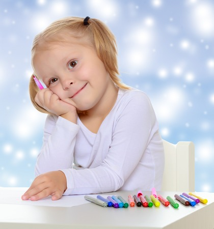 shool: Pretty little blonde girl drawing with markers at the table.Girl put head on his hand , she dreams about something.The concept of celebrating the New year, Holy Christmas Stock Photo