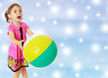 Emotional little girl with pigtails on the head, in a pink dress. Girl catches with hands a large, inflatable striped ball.On new year or Christmas blue background with white big stars.