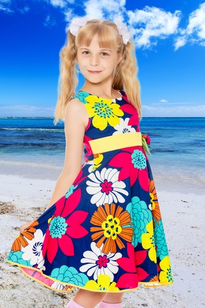 Beautiful little girl with long blonde ponytails on the head and white bows in bright summer dress keeps the dress over the edge.On the background of sea beach, warm sea and blue sky with clouds.
