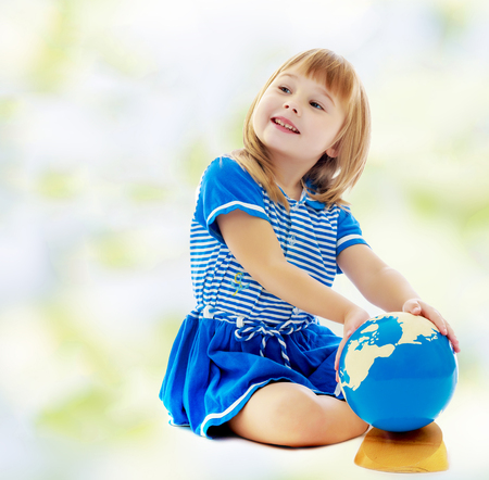 The concept of changing seasons in the life of a child. On the green and white blurred background. Nice little girl in a Sea blue dress sitting on the floor. Girl turns hand the globe.