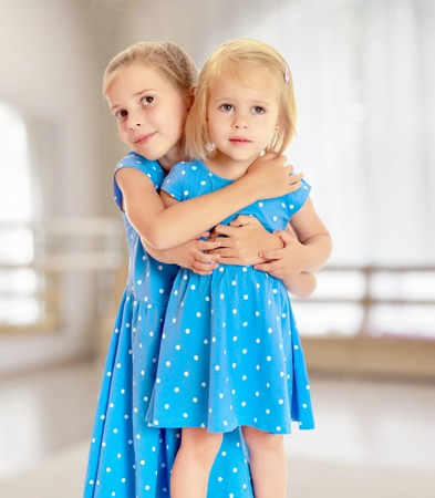 identical: Two charming little girls, sisters , in identical blue dresses with polka dots , cuddling. Stock Photo