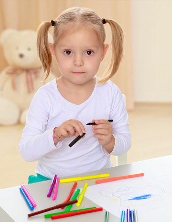 shool: Pretty little blonde girl drawing with markers at the table.Girl holding in hands blue marker.