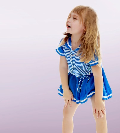On a purple background, smooth transition from dark to light. Cute little unkempt girl in a short blue dress. Girl looking to the side with his hands on his knees. Stock Photo