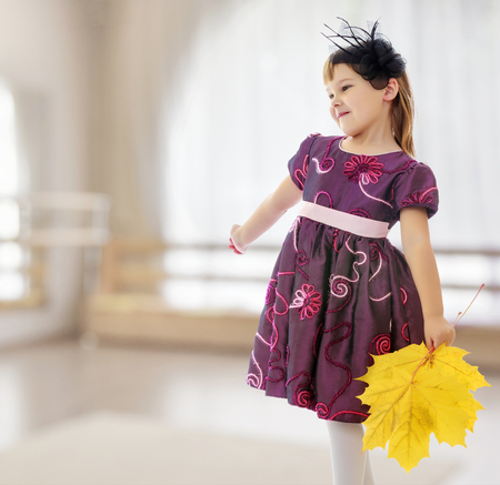 In a room with a large semi-circular window. Caucasian little girl dressed in brown dress. She is holding a bouquet of maple leaves. Turning sideways to the camera.