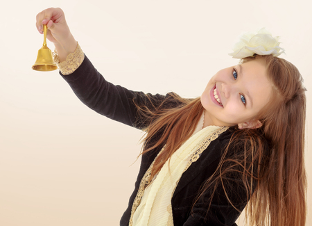 little bell: Joyful little long-haired girl with a white rose in her hair, rings the bell. Close-up.Brown gradient background. Stock Photo