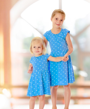 identical: Two charming little girls, sisters , in identical blue dresses with polka dots , cuddling.On the background of the hall with large semi-circular window.
