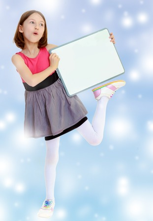 Emotional a small, thin girl, holding a front of a white poster. She stands on one leg.Blue Christmas festive background with white snowflakes. Stock Photo