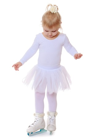 skids: Happy little girl , future skater, white sports dress and white figure skates on two skids -Isolated on white background Stock Photo