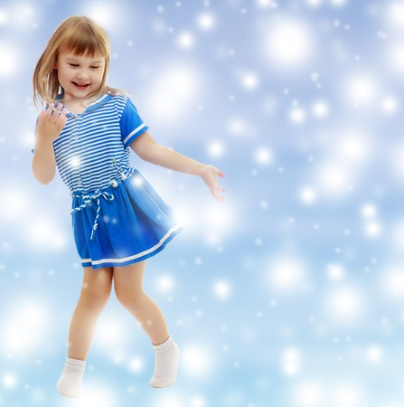 On a blue background with white blurry circles, like Christmas snowflakes. Gentle little girl in a short blue dress similar to a sailor suit, with pleasure poses for the camera.