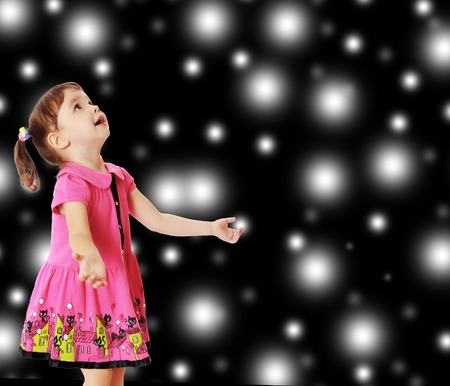 Adorable little girl with pigtails on the head, in a pink dress. The girl was looking at the top turned sideways to the camera.On new years, Christmas or a black background