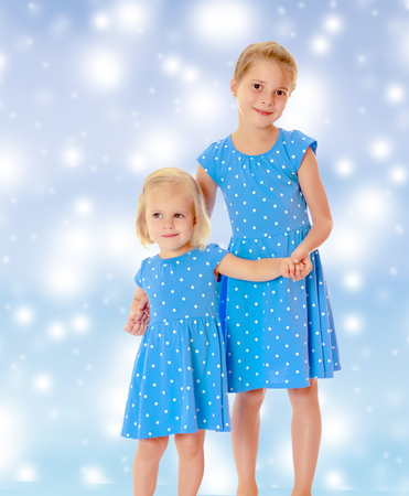 identical: Two charming little girls, sisters , in identical blue dresses with polka dots , cuddling.On a blue background with large, white, Christmas or new years snowflakes.11