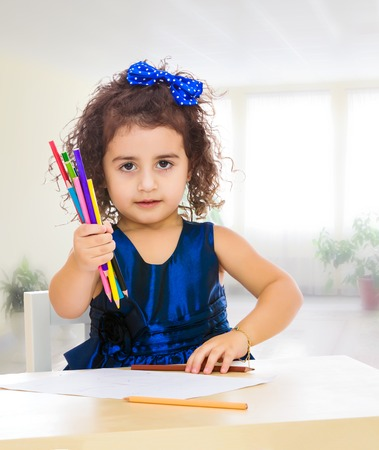 Cute little girl in blue dress, holds a lot of pencils . She paints at a table in a Montessori kindergarten.In the room with a big bright window.