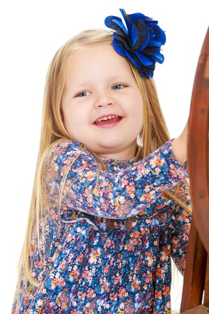 Joyful little round-faced girl with long blonde hair below the shoulders,which are attached to a large blue flower . close-up - Isolated on white background Stock Photo