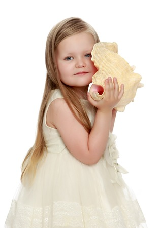 Happy little round-faced girl with long, blonde hair below the shoulders, in a white dress. Girl put your ear to a large sea shell. She listens to the sound of the sea. Close-up
