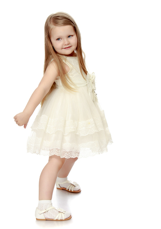 Lovely little round-faced girl with long, blonde hair below the shoulders, in a white dress - Isolated on white background