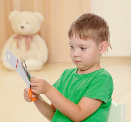 shool: The concept of preschool development of the child ,against a childs room where in the background a Teddy bear.Pensive little boy cut with scissors a piece of cardboard. Stock Photo