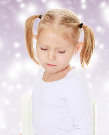 shool: The concept of celebrating the New year, Holy Christmas, or childs birthday on a purple background and white snowflakes.Distressed small, blonde girl with white t-shirts without a pattern.