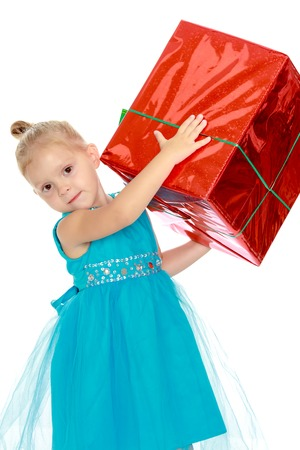 lifted hands: Caucasian little girl in a blue dress, holding the hands of the big red box that is a gift.The girl lifted the box over his head.Isolated on white background Stock Photo