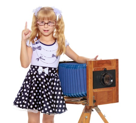 Adorable little blond girl wearing glasses and fancy dress polka dot advertises the old wooden camera-Isolated on white background
