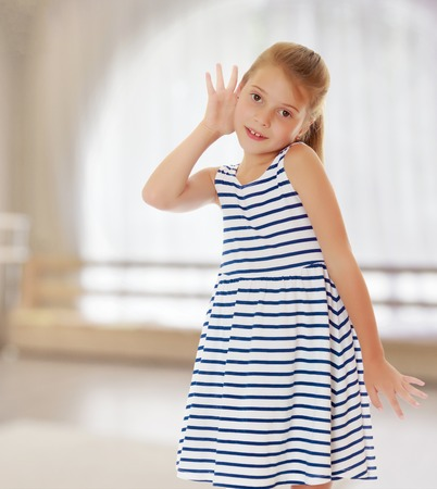 Caucasian little girl in a striped summer dress, listening. Girl holding a hand to his ear.On the background of the hall with large semi-circular window. Stock Photo