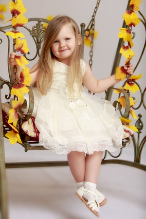 Adorable little round-faced girl with long, blonde hair below the shoulders, little Princess in a white dress. Girl swinging on a swing