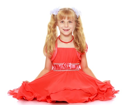 ponytails: A beautiful little Caucasian girl with long, blonde ponytails on her head in a bright orange dress . Sat down on the floor-Isolated on white background Stock Photo