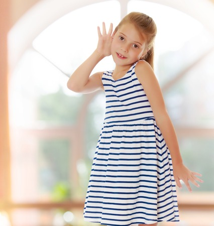 On the background of the hall with large semi-circular window.Caucasian little girl in a striped summer dress, listening. Girl holding a hand to his ear.