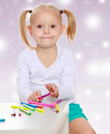 shool: Pretty little blonde girl drawing with markers at the table.Girl holding in hands a pink marker.The concept of celebrating the New year, Holy Christmas, or childs birthday on a purple