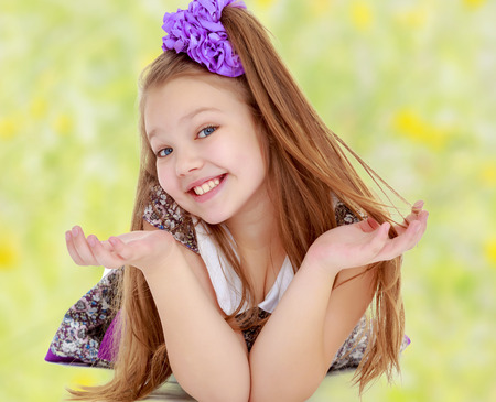 sweetly: Happy little girl with a big purple bow on her head lying on the floor. Girl throws hands and smiling sweetly at the camera.Summer blurred green background with yellow flowers.