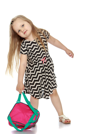 Cute little girl picks up the strap for the backpack - Isolated on white background Stock Photo