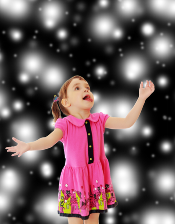 Surprised little girl raised his head up and gesturing with his hands. Close-up.On new years , Christmas or a black background where glowing large white star. Stock Photo