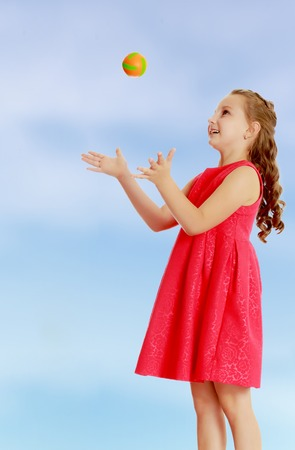 Beautiful Caucasian little girl in a bright orange dress, throws a little ball.On the pale blue background.
