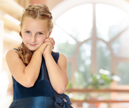 Cute little Caucasian girl in a dark blue dress, folded her hands near the face . close-up.In a room with a large semi-circular window.