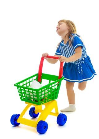 Niña alegre en vestido azul con el carro de compras. Aislado en el fondo blanco. Foto de archivo