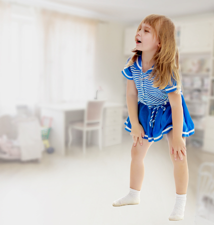 unkempt: Cute little unkempt girl in a short blue dress. Girl looking to the side with his hands on his knees.In the rooms, with a Desk and long shelves on which stand toys.