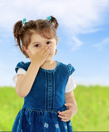 Unhealthy little girl with short pigtails on her head, closed his nose with his hand, the girl sneezes from allergies. Close-up.On the background of green grass and blue sky with clouds. Stock Photo