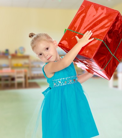 Caucasian little girl in a blue dress, holding the hands of the big red box that is a gift.The girl lifted the box over his head.The concept of pre-school education of the child among their peers Stock Photo