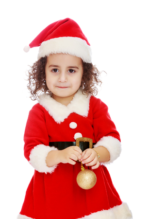 Very cute ,with curly hair little girl in a suit and cap of Santa Claus , is holding a Christmas toy. Close-up.Isolated on white background.