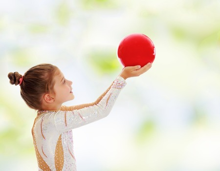 Cute little girl gymnast turned sideways to the camera , holding in his outstretched hands a red ball.On blurred, abstract, green background Stock Photo