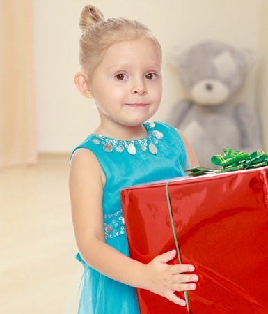 shool: The concept of preschool development of the child ,against a childs room where in the background a Teddy bear.Caucasian little girl in a blue dress, holding the hands of the big red box Stock Photo