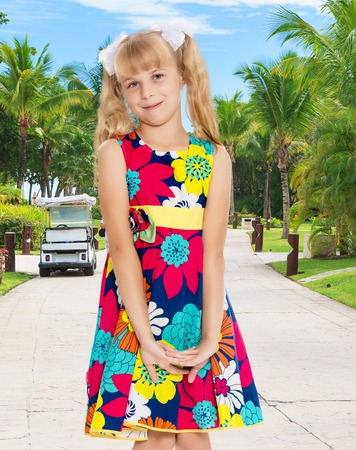 ponytails: Beautiful little girl with long blonde ponytails on her head tied with white bows, bright summer dress and knee socks.On the background of the road, palm trees and blue sky with clouds. Stock Photo