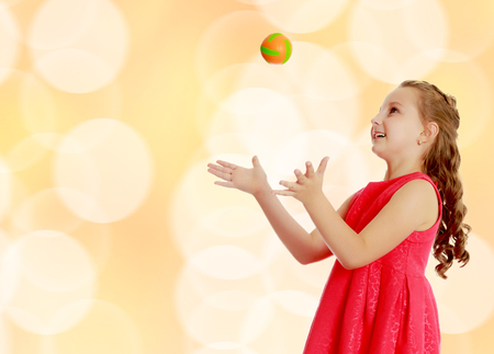 Beautiful Caucasian little girl in a bright orange dress, throws a little ball.Brown festive, Christmas background with white snowflakes, circles. Archivio Fotografico