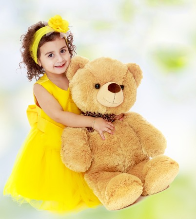 Joyful little girl in a yellow dress and bow on her head sitting on the floor. Girl hugging a big Teddy bear.white-green blurred abstract background with snowflakes. Stock Photo
