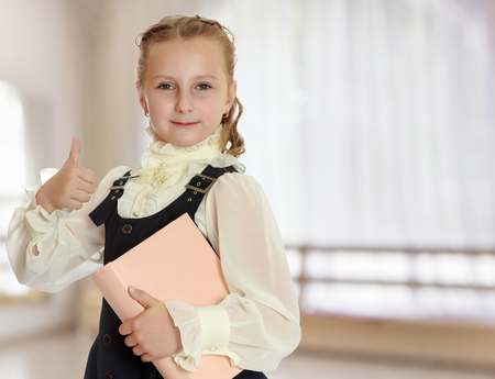 Dressy girl schoolgirl in black dress and white blouse holding a textbook and shows thumb. Gesture all right. Close-up.In a room with a large semi-circular window.
