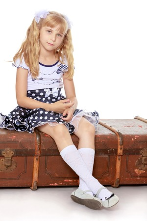 ponytails: Tired little girl with long blonde ponytails on her head, sitting on the old road suitcase-Isolated on white background