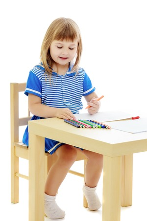 Nice little blonde girl in a blue dress. Girl sitting at table and drawing with markers.Isolated on white background. Stock Photo
