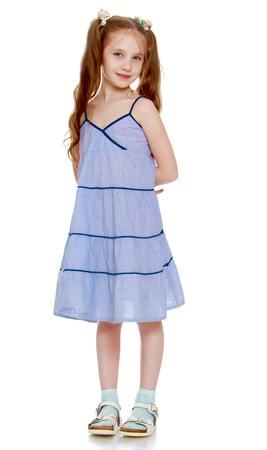 zapatos escolares: niña suave con largas trenzas hasta la cintura y los arcos blancos trenzados. En un vestido largo azul. Tiene las manos detrás de la espalda - aislado en el fondo blanco