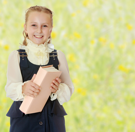 dressy: Dressy girl schoolgirl in black dress and white blouse holding a textbook and smiling cheerfully at the camera. Close-up.Summer white green blurred background.