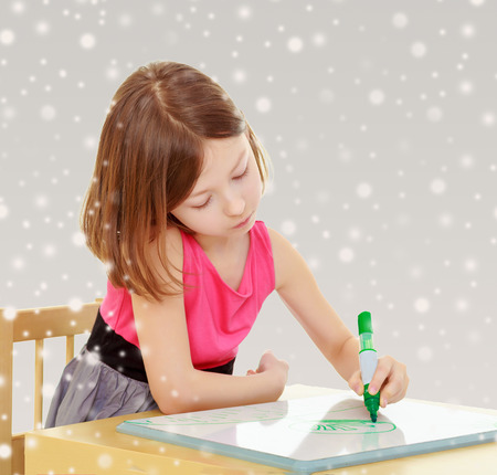 Little girl schoolgirl sits and draws at the table,green marker on the white Board. Gray background with round white snowflakes.