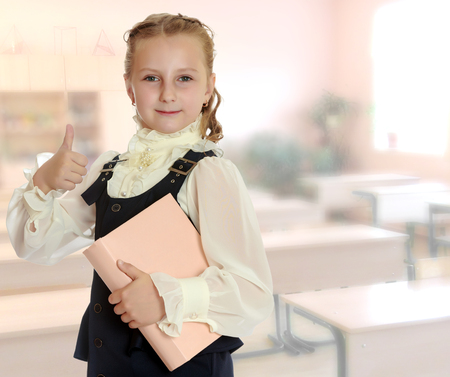 dressy: Dressy girl schoolgirl in black dress and white blouse holding a textbook and shows thumb. Gesture all right. Close-up.During a lesson in school. Stock Photo